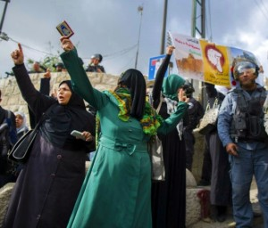 Israeli police officers guard as Palestinian women take part in a protest after authorities restricted access to the compound known to Muslims as Noble Sanctuary and to Jews as Temple Mount outside Jerusalem's Old City on October 15, 2014. width=
